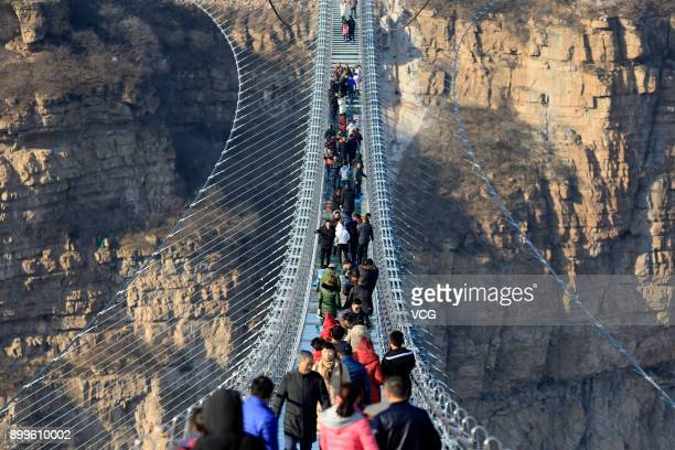 Tourists walk on the glassbottomed suspension bridge at Hongyagu Scenic Area on December 26 2017 in Pingshan Hebei Province of China The 488meterlong...