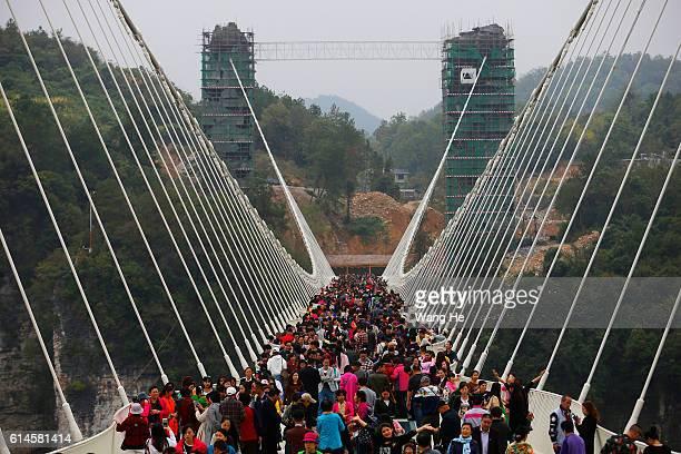 Tourists walk on the glass-floor suspension bridge in Zhangjiajie in south China's Hunan province on October 14, 2016 in Zhangjiajie, China. The...