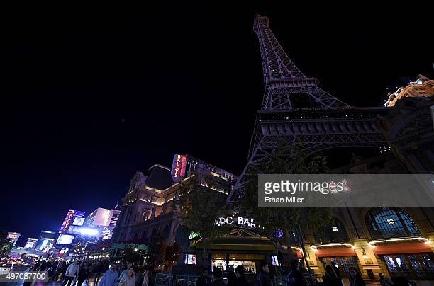 Tourists walk on the Las Vegas Strip in front of the Paris Las Vegas' 50story Eiffel Tower replica which was dimmed in a show of solidarity with...