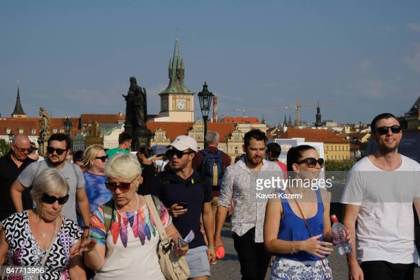 Tourists walk on the pedestrian Charles Bridge with the old city view in the background on a sunny summer day on July 18 2017 in Prague Czech...
