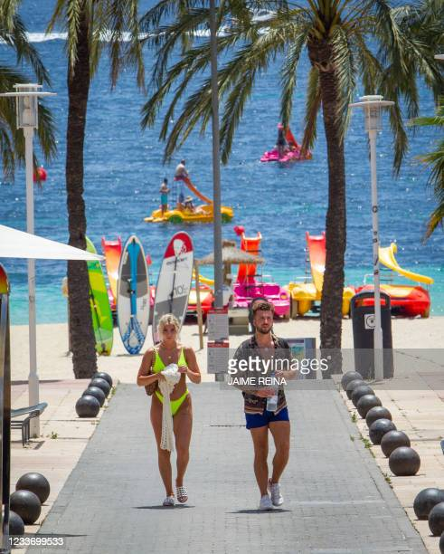 Tourists walk on the promenade at Magaluf Beach in Calvia, on the Balearic Island of Mallorca, on June 28, 2021. - British holidaymakers heading to...