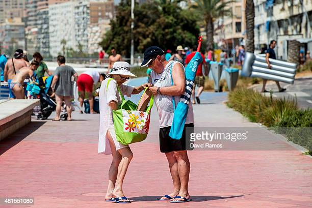 Tourists walk on the promenade at Poniente Beach on July 22 2015 in Benidorm Spain Spain has set a new record for visitors with 292 million visitors...