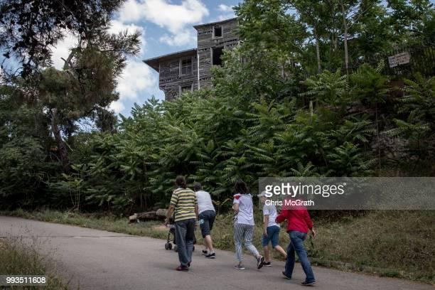 Tourists walk on the road underneath the dilapidated Prinkipo Greek Orthodox Orphanage on July 7 2018 in Buyukada Turkey The historic...