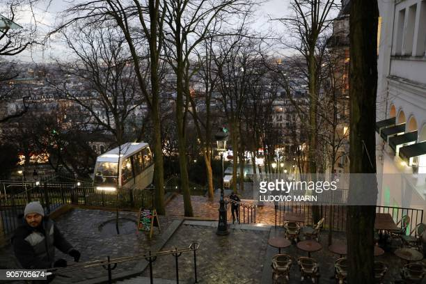 Tourists walk on the stairs of Montmartre hill next to the funicular on january 16 in Paris on January 16 2018 / AFP PHOTO / ludovic MARIN