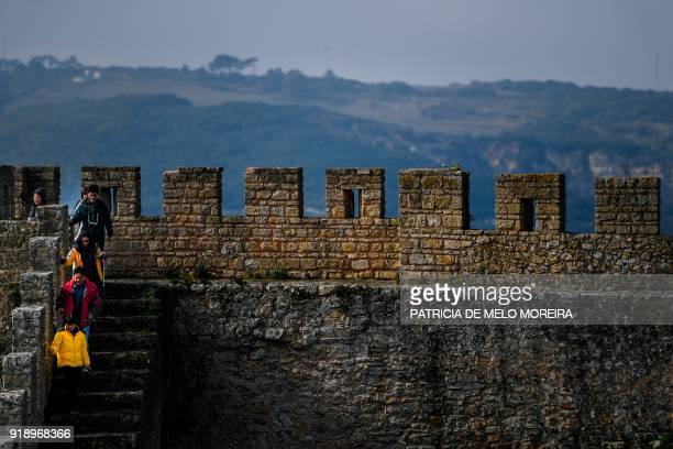 Tourists walk on the walls surrounding the medieval town of Obidos central Portugal on February 9 2018 / AFP PHOTO / PATRICIA DE MELO MOREIRA