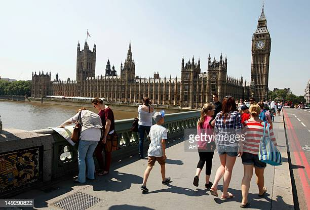 """Tourists walk on Westminster Bridge in front of the """"Big Ben"""" clock Tower, July 26, 2012 in London where the London 2012 Olympic Games opening..."""