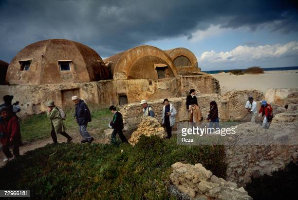 Tourists walk past 3rd century 'Hunting Baths' named for a fresco discovered inside part of the ruins of Leptis Magna the largest city of the ancient...