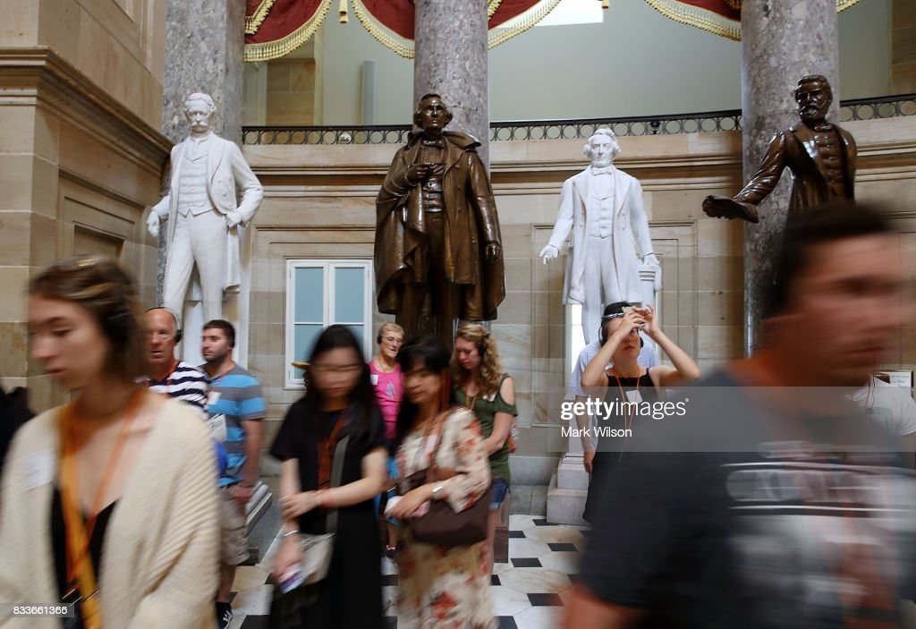 Tourists walk past a bronze statue of Confederate president Jefferson Davis (2ndL) that stands inside of Statuary Hall at the US Capitol August 17, 2017 in Washington, DC. Virginia Governor Terry McAuliffe said he would like to remove all Confederate statues in the wake of a deadly white nationalist rally in Charlottesville.