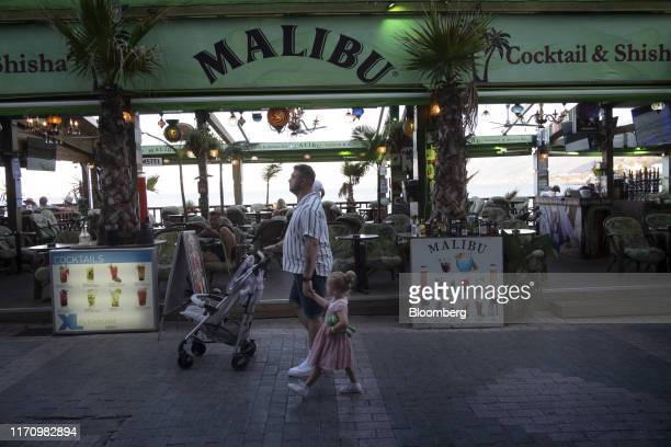 Tourists walk past a cocktail bar by the sea in Hersonissos, on the island of Crete, Greece, on Tuesday, Sept. 24, 2019. Like Crete, Europes other...