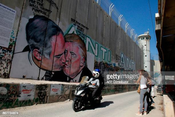 Tourists walk past a graffiti by street artist Lushsux depicting US President Donald Trump kissing Israeli Prime Minister Benjamin Netanyahu drawn on...