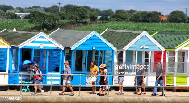 Tourists walk past a line of colourful beach huts Southwold With the beaches in England now fully opened with only social distancing measures in...