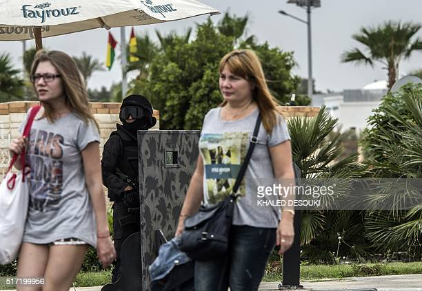 Tourists walk past a member of the Egyptian special forces outside the venue during a conference for defence ministers and officials of the 27...