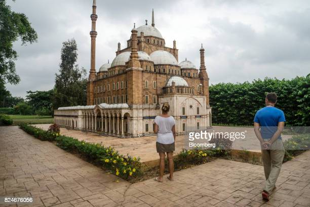 Tourists walk past a miniature replica of Egypt's Mosque of Muhammad Ali at the Islamic Heritage Park in Kuala Terengganu Terengganu Malaysia on...