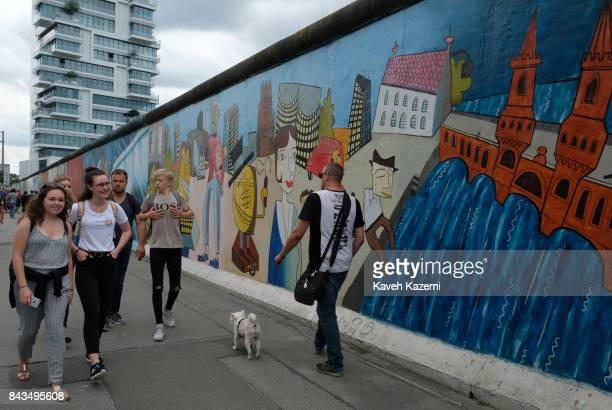 Tourists walk past a mural in The East Side Gallery on July 16 2017 in Berlin Germany The East Side Gallery is a1316 meter long section of the Berlin...