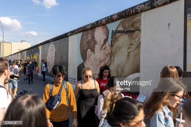 Tourists walk past a mural showing Soviet leader Leonid Brezhnev kissing East German President Erich Honecker at the East Side Gallery, on July 03,...