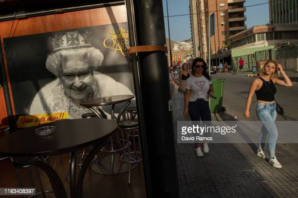 Tourists walk past a portrait of Queen Elizabeth II on July 21 2019 in Benidorm Spain More than 39 million of tourists are expected to visit Spain by...