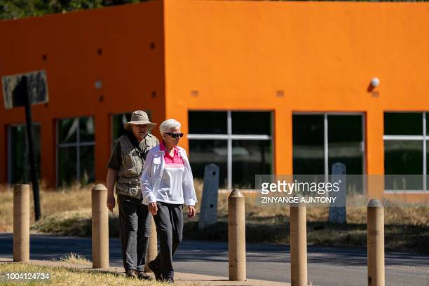 Tourists walk past a recently built infrastructure on June 29 2108 in the resort town of Victoria Falls After nearly two decades in the doldrums...