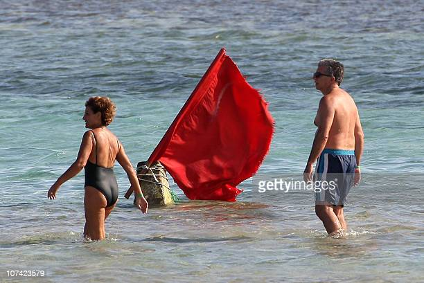 Tourists walk past a red flag serving as a warning of shark sightings on a beach in the Red Sea resort of Sharm elSheikh on December 8 2010 Marine...