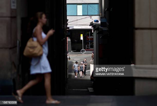 Tourists walk past an alley on the main shopping street in Sydney on December 28 2012 International visitors to Australia are expected to increase...