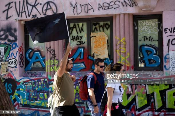 Tourists walk past an intervened wall in Santiago Chile on January 10 2020 A free walking tour of the ground zero of the protests seeks to explain...