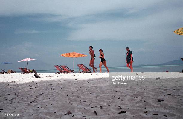 Tourists walk past deck chairs in Maya Bay on Ko Phi Ph in the South of Thailandi Brilliant turquoise sea and white sparkling sandy beaches have made...