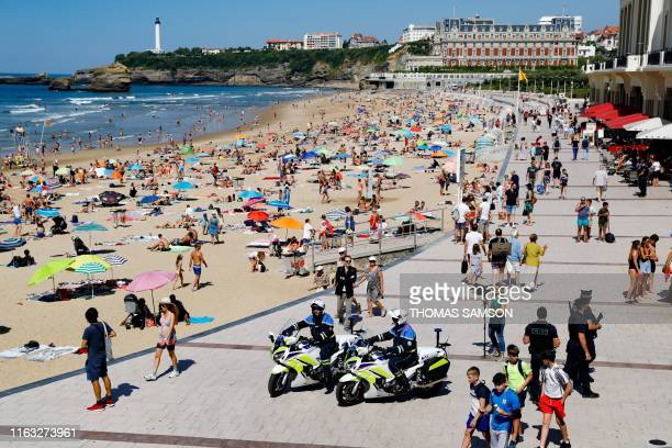 Tourists walk past French national policemen on motorcycles who patrol along the Grande Beach in Biarritz southwestern France on August 22 where G7...