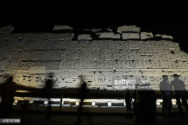 Tourists walk past hieroglyphics at Karnak temple in Luxor a town 700 kilometres south of the Egyptian capital Cairo in the evening of June 11 2015...