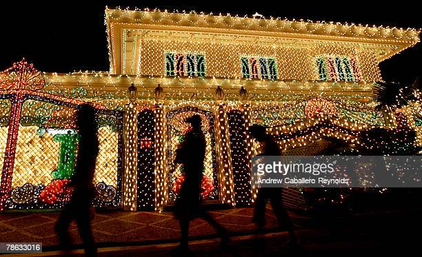 Tourists walk past houses lit up on Policarpio street, which has been holding a Christmas light show for the past 12 years, in Mandaluyong, a suburb...
