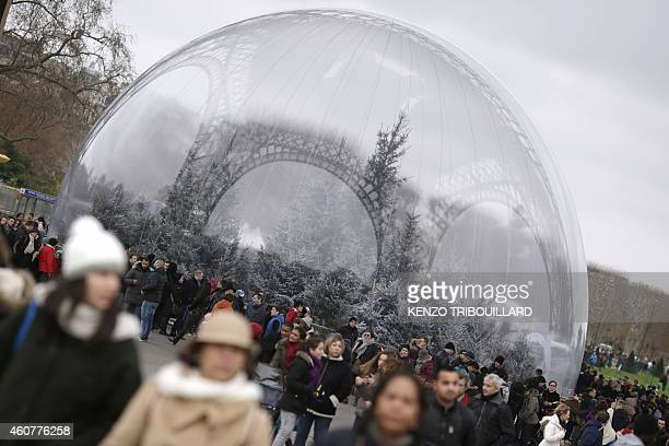 Tourists walk past Pine trees displayed in a giant snow globe for Christmas at the Eiffel Tower in Paris on December 22 2014 A strike by sales staff...