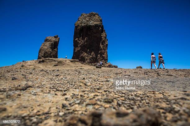 Tourists walk past Roque Nublo a volcanic rock on July 26 2015 near Tejeda in Gran Canaria Spain Gran Canaria island part of the Canary Islands is...