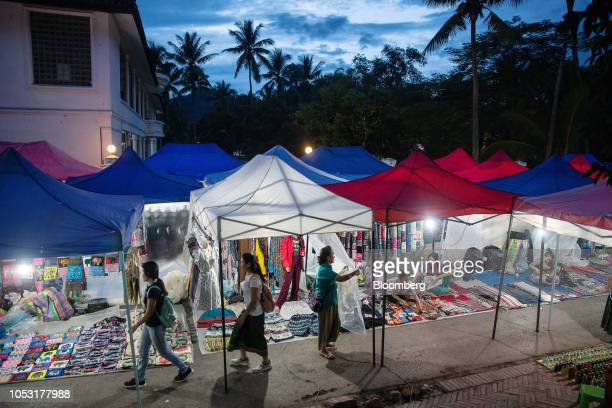 Tourists walk past stalls at the Night Market in Luang Prabang Laos on Sunday Oct 21 2018 Laos's economy is set to expand at 7 percent this year...