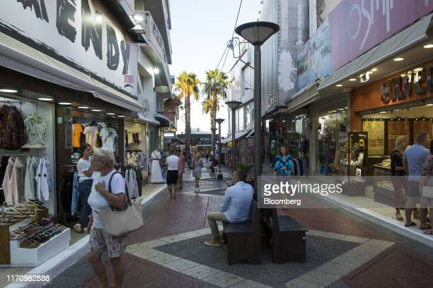 Tourists walk past stores along a street in Hersonissos, on the island of Crete, Greece, on Tuesday, Sept. 24, 2019. Like Crete, Europes other...