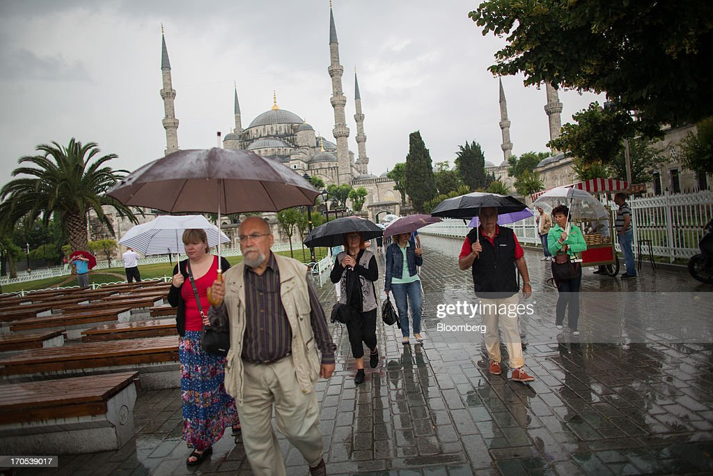 Tourists walk past the Blue Mosque, also known as the Sultan Ahmed, in Istanbul, Turkey, on Friday, June 14, 2013. The law forbids the sale of alcohol at night and near schools and mosques, going against the secular traditions of the Muslim-majority country of 74 million, where many people drink and women often choose not to cover their hair. Photographer: Lam Yik Fei/Bloomberg via Getty Images
