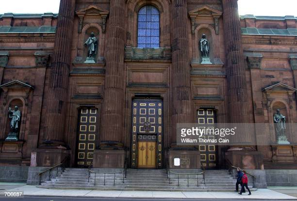 Tourists walk past the Cathedral Basilica of Saints Peter and Paul March 22 2002 in Philadelphia PA A priest in the Philadelphia Archdiocese has been...