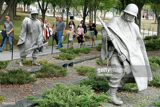 Tourists walk past the Korean War Memorial July 5 2007 in Washington DC Each year thousands of tourists visit the monuments and many attractions at...