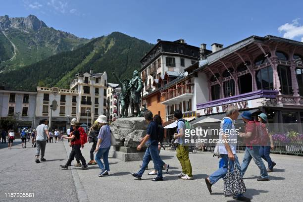 Tourists walk past the statue of Jacques Balmat, first conqueror of the Mont-Blanc, on July 20 in a street of Chamonix, French Alps. - The Brevent...