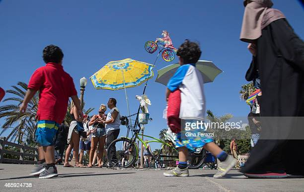 """Tourists walk past the tricked-out tricycle belonging to the """"Bird Man of Santa Monica"""" Howard Kaminsky while visiting Palisades Park at the Santa..."""
