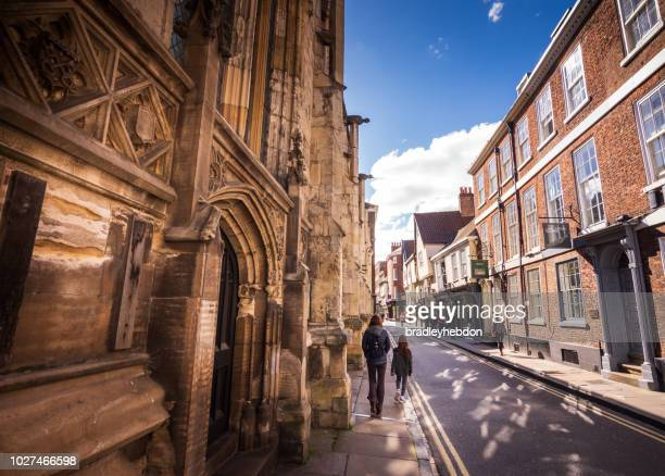 tourists walk past the york minster cathedral in york, uk - york stock photos and pictures
