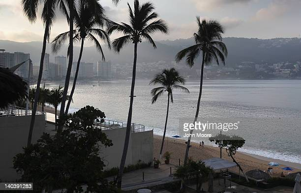 Tourists walk the beach early on March 2 2012 in Acapulco Mexico Drug violence surged in the coastal resort last year making Acapulco the second most...