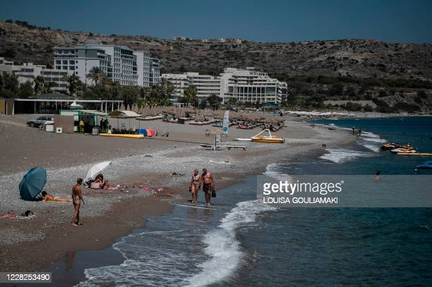 Tourists walk the beach in front of hotels on the Aegean island of Rhodes on August 29, 2020. - Rhodes island, one of the mass tourism Greek islands...