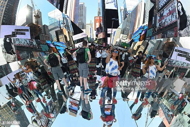 Tourists walk through a three mirrored surface a floor and two angled walls interactive installation by Cuban artist Rachel Valdés Camejo titled The...