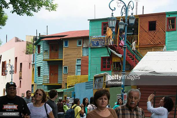 Tourists walk through Caminito a narrow traditional street in La Boca Buenos Aires Argentina on Sunday Nov 10 2013 Argentina needs to slow inflation...