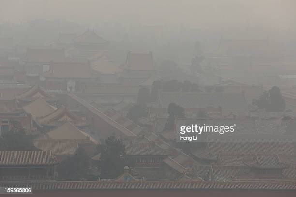 Tourists walk through the door of the Forbidden City as pollution covers the city on January 16 2013 in Beijing China Heavy smog shrouded Beijing...