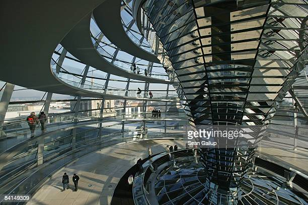 Tourists walk through the glass cupola of the Reichstag on December 31 2008 in Berlin Germany According to a recentlyreleased report Berlin is...