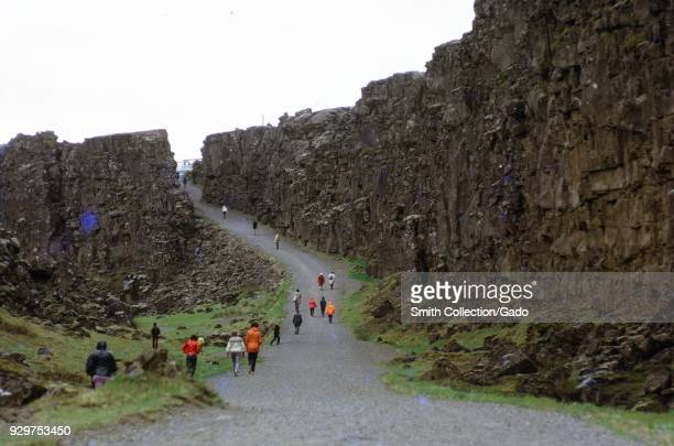 Tourists walk through Thingvellir a national park in Iceland on an overcast day 1970