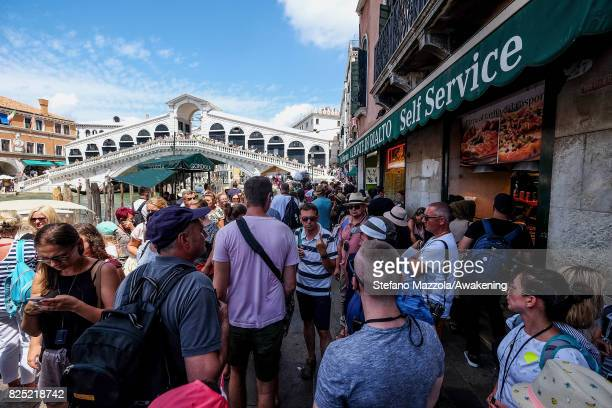 Tourists walk towards Rialto bridge on August 1 2017 in Venice Italy Over 30 million tourists visit the 3 mile by 2 mile city of Venice each year...