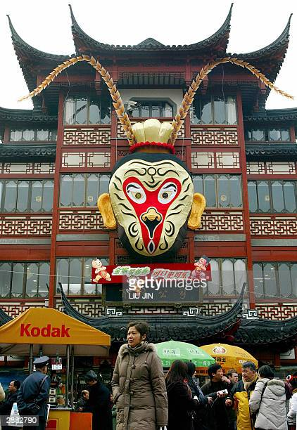 Tourists walk under a huge ornament of Monkey King at Shanghai's Yu Garden 20 January 2004 ahead of Chinese Year of the Monkey Although China's Lunar...
