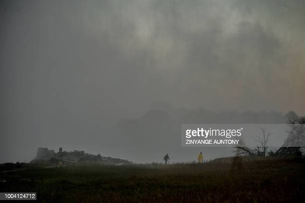 Tourists walk under a thick cloud of vapour rising from the gorge covering the in the rainforest overlooking the waterfalls on June 29 2018 in...