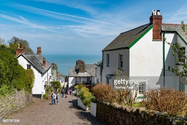 Tourists walk up a steep street in historic village Clovelly in Devon