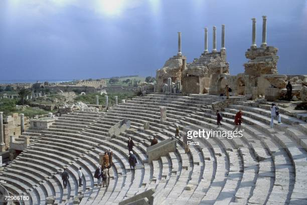 Tourists walk up steps of the theater's tiered seating area which provides views of the expansive city ruins of Leptis Magna the largest city of the...